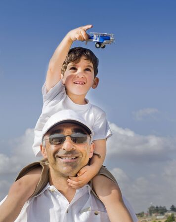 boy on father shoulders with toy airplane Stock Photo