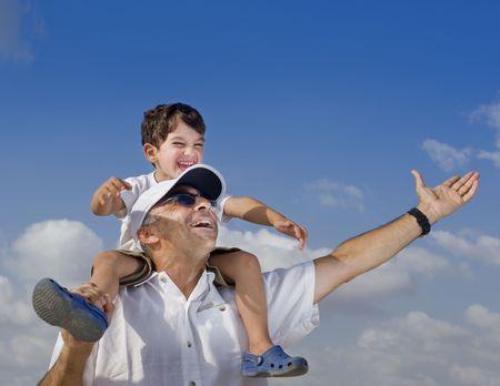 shoulder ride: hijo de montar sobre sus hombros padre con los brazos abiertos Foto de archivo