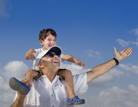 man carrying: son riding on his father shoulders with spread arms