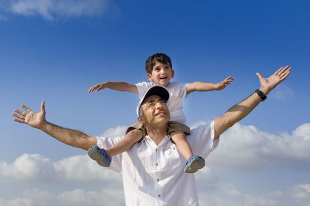 son riding on his father shoulders with spread arms  photo