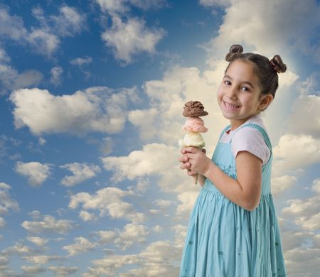 little girl holding three flavors ice cream scoops on cone with clouds photo