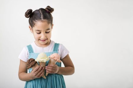 3 persons only: little girl holding three cones with chocolate, vanila and strawberry ice cream scoops
