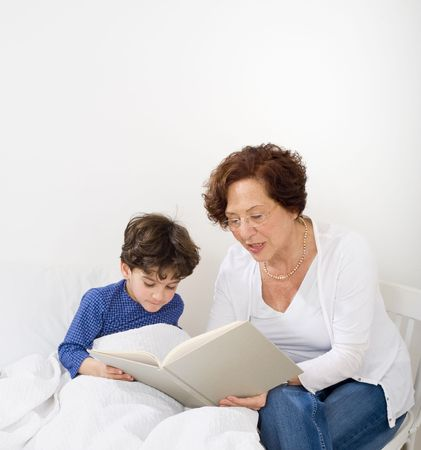 grandmother reading to grandchild a bed time story Stock Photo