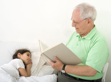 grandfather reading to grandchild a bed time story