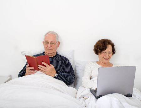 senior couple in bed with laptop and book photo