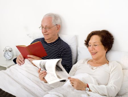 senior couple in bed with newspaper and book photo