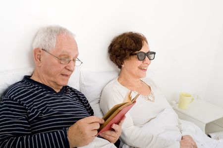 senior couple in bed man reading woman watching 3D TV with special glasses Stock Photo