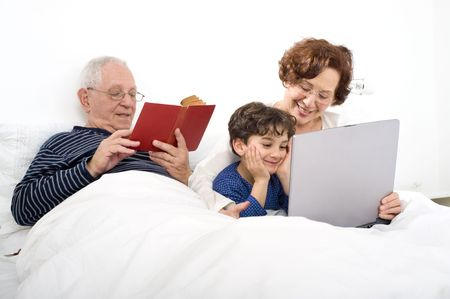 grandparents with grandchild on bed with a laptop computer photo
