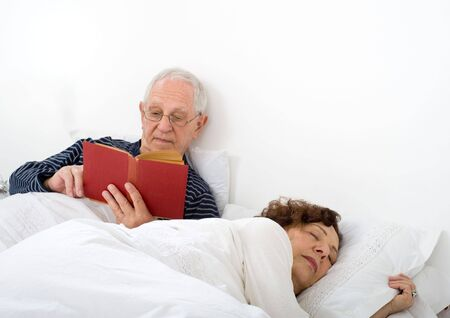 senior couple in bed man reading and woman is asleep photo