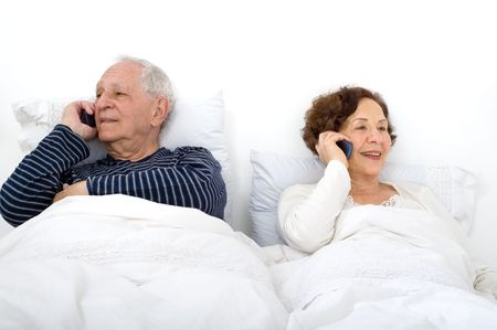 senior couple in bed talking on the phone photo