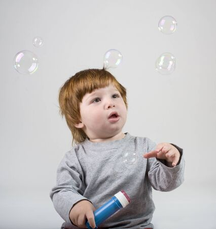 little redhead boy playing with soap bubbels Stock Photo - 7222759