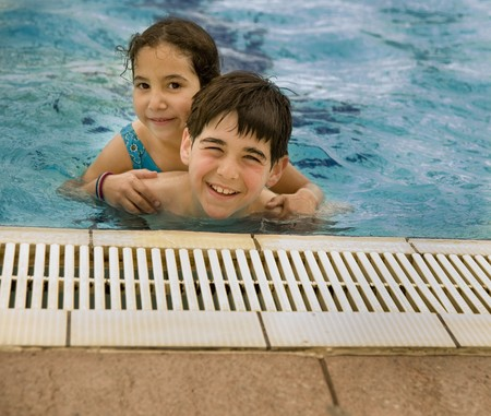 Boy carrying girl by piggyback in the pool photo