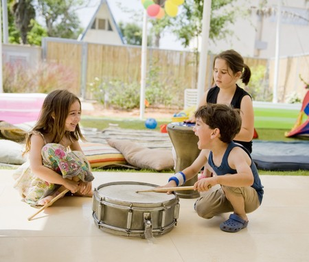 kid sitting: three kids in the backyard having fun with drums.