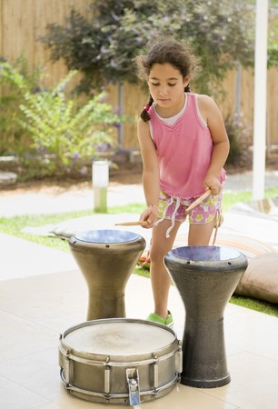 little girl playing drums in backyard
