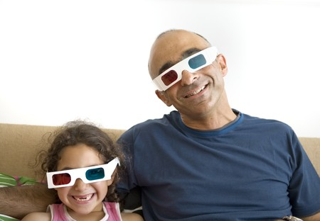 Father and daughter watching television in 3D wearing red and blue glasses photo