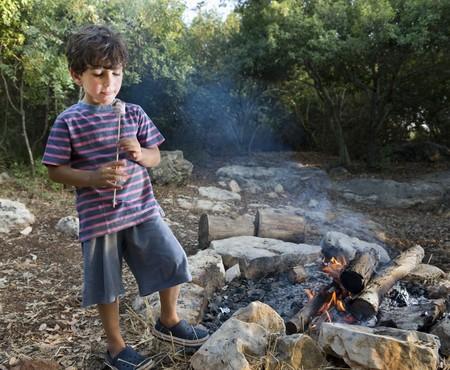 boy having marshmallow at the campfire photo