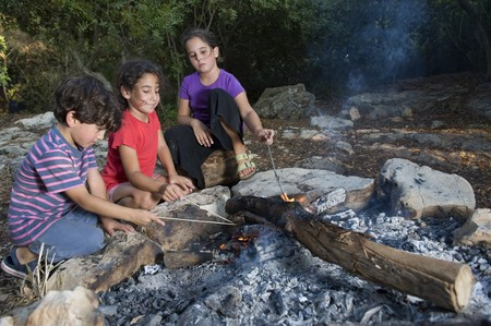 three kids in a campfire in a mediterranean forest Stock Photo