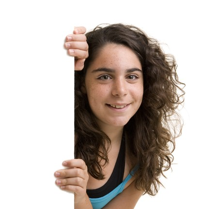 young girl peeking behind a white wall/sign. Stock Photo - 7666649