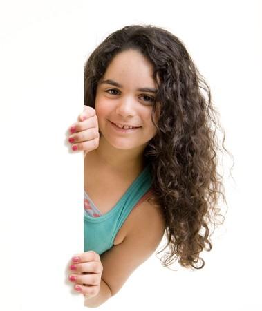 young girl peeking behind a white wallsign. photo