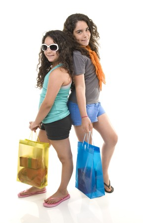 two young girls with shopping bags isolated on white. photo