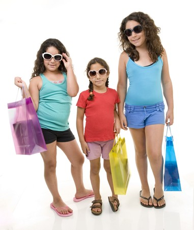 three young girls with shopping bags isolated on white. photo