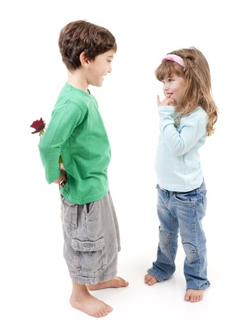 young boy hiding a rose behind his back smiling to a little girl photo