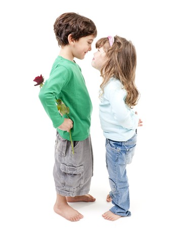 young boy hiding a rose behind his back smiling to a little girl