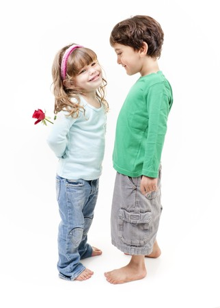 little boy and girl: young girl hiding a rose behind her back smiling to a little boy