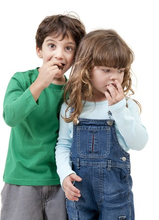 Two kids eating a brownie cake isolated on white