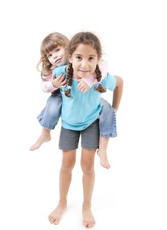 two girls piggyback isolated on white photo
