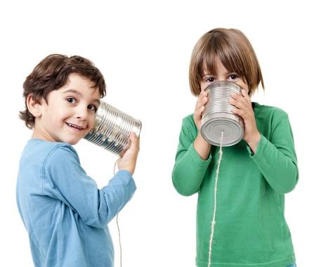 dos personas conversando: Dos muchachos hablando por un tel�fono de lata aislado en blanco  Foto de archivo