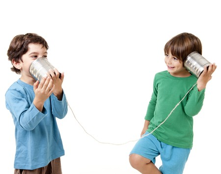 Two boys talking on a tin can phone isolated on white photo