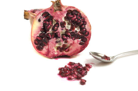 Close-up on a fresh pomegranate with yummy juice and sweet and sour seeds, isolated on white