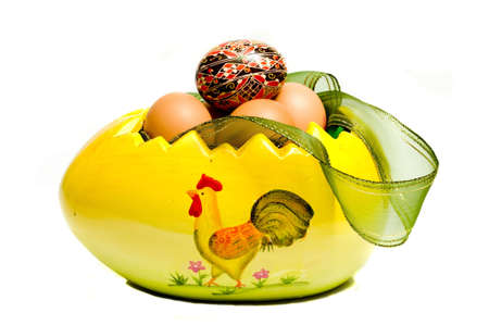 close-up on a huge yellow easter egg filled with eggs, isolated on white photo