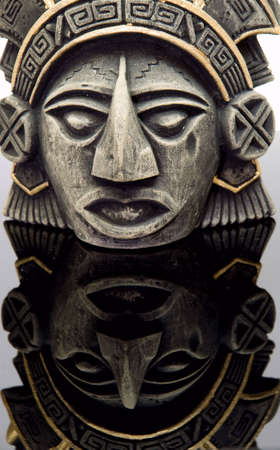 maya religion: mayan mask close-up, reflected on a neutral surface Stock Photo