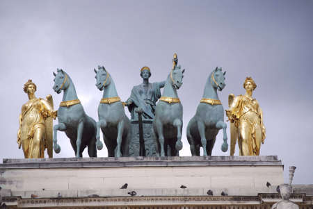 blue and gold sculpture of a carriage with four horses in paris photo