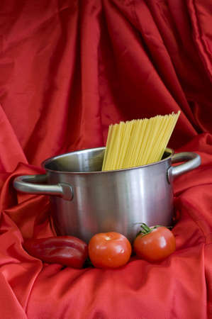 shiny silver pot and spaghetti, on red background photo