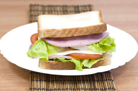 yummy and fresh turkey ham sandwich with lettuce, swiss cheese and tomato photo