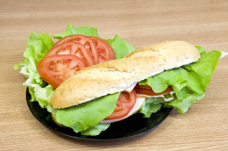 delicious and fresh sesame baguette with turkey, cheese, lettuce and tomatoes photo