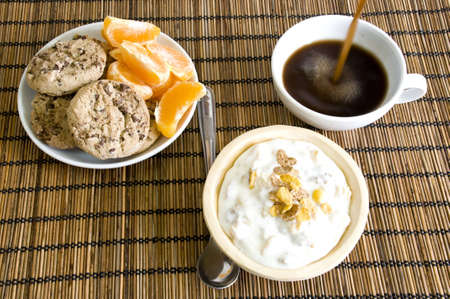 breakfast setup, pouring coffee, yoghurt, cookies and fruits Stock Photo