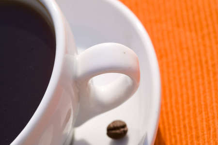 closeup on a coffee cup on orange background