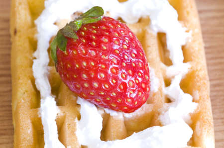 closeup on strawberry and whip cream waffle