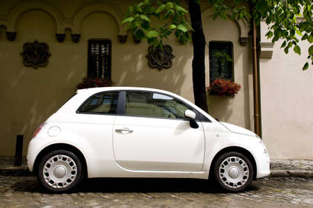 show window: cute white small car, urban view Stock Photo