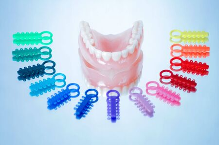 ligature: Dentures surrounded by multicolored orthodontic ligature ties Stock Photo