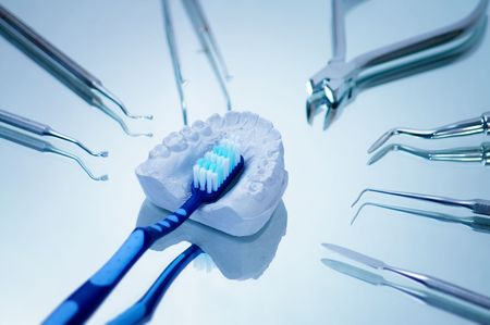 Toothbrush and gypsum dentures surrounded by dental instruments