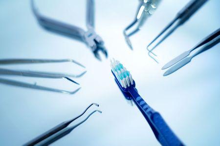 prosthodontics: Spazzolino circondato da strumenti odontoiatrici con molto poca profondit� di campo  Archivio Fotografico