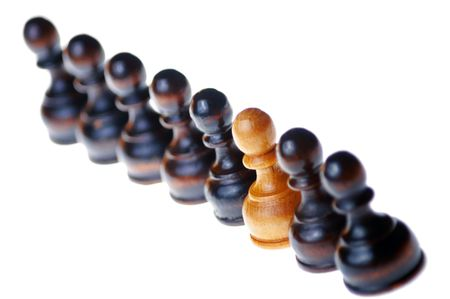 adversaries: White pawn standing out in a row of black pawns , isolated on white , selective focus Stock Photo