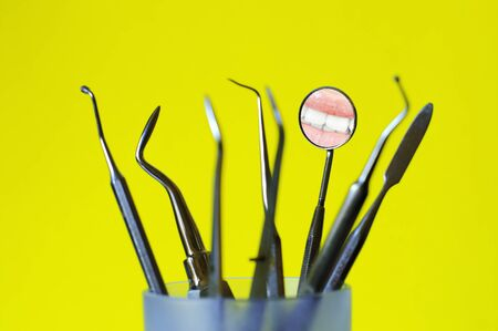 Angled mirror with smile reflection and dental tools in a glass , yellow background