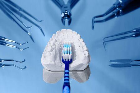 dentadura postiza: Cepillo de dientes y yeso molde dental rodeado de instrumentos odontol�gicos