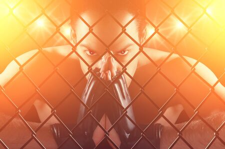 Cage fighter concentrating , staring at the camera , dramatic lighting